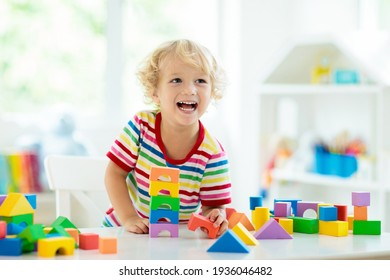 Kid playing with colorful toy blocks. Little boy building tower of block toys. Educational and creative toys and games for young children. Baby in white bedroom with rainbow bricks. Child at home. - Shutterstock ID 1936046482