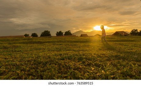 kid playing at the field during sunset