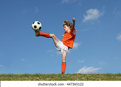 kid playing football or soccer kicking ball