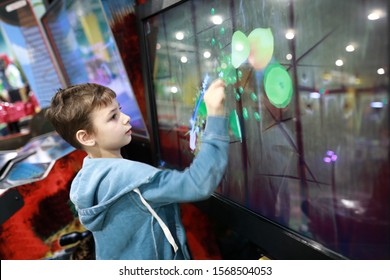Kid playing game on touchscreen in entertainment park