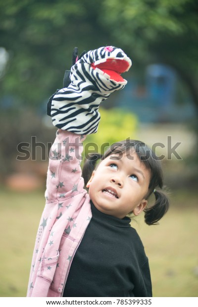 kid playing with hand puppet doll