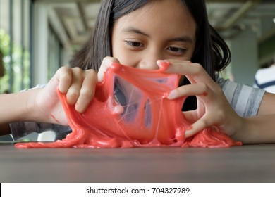 Kid Playing Handmade Toy Called Slime, Selective focus on Eyes, Teenager having fun and being creative homemade slime