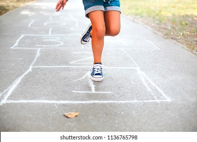 Kid playing hopscotch on playground outdoors, children outdoor activities