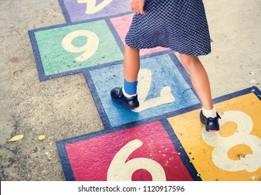 Kid playing hopscotch at school