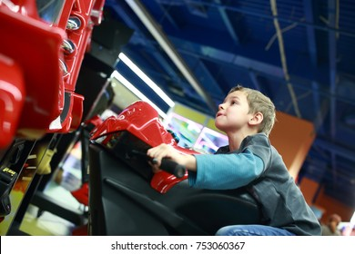 Kid playing in motorcycle simulator at indoor playground