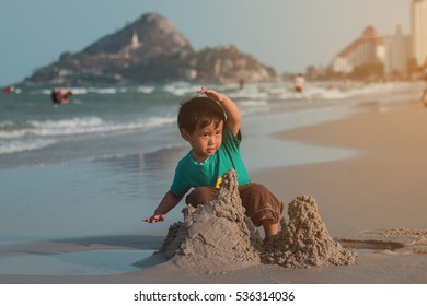 kid playing on beach to build sand castle at sunset with family trip