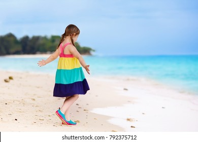 Kid playing on tropical beach. Child running and dancing at sea shore. Kids play on ocean coast. Water and sand fun for children. Summer dress fashion for little girl. Family summer beach vacation.