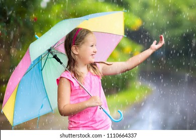 Kid playing out in the rain. Children with umbrella play outdoors in heavy rain. Little girl caught in first spring shower. Kids outdoor fun by rainy autumn weather. Child running in tropical storm.