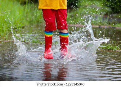 Kid playing out in the rain. Children with umbrella and rain boots play outdoors in heavy rain. Little boy jumping in muddy puddle. Kids fun by rainy autumn weather. Child running in tropical storm.