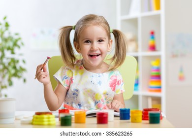 kid playing and painting at home or kindergarten or playschool
