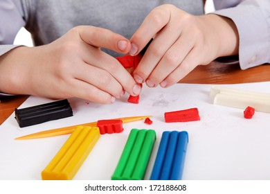 Kid playing with Plasticine at the School Desk Closeup