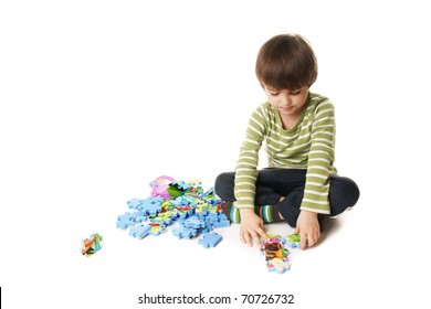Kid playing with puzzle isolated on white background