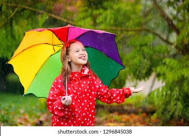 Kid playing in the rain in autumn park. Child with umbrella and rain boots play outdoors in heavy rain. Little girl in red jacket under fall shower. Kids fun by rainy weather. Children play in storm.