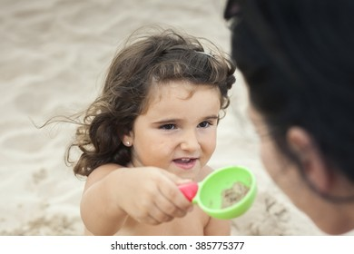 Kid playing with the sand in the beach with her mother.