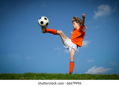 kid playing soccer kicking football