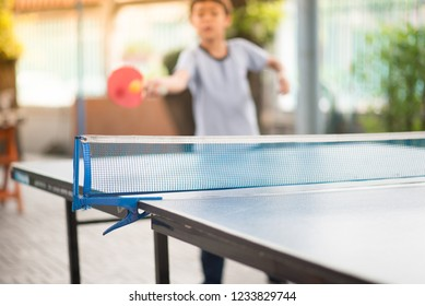 Kid playing table tennis outdoor with family