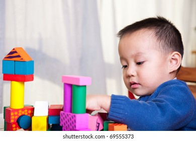 kid playing with toy blocks