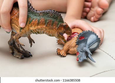 kid playing with toys of acrocanthosaurus and triceratops bloody body on sofa at home