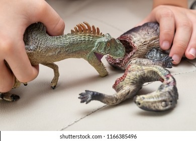 kid playing with toys of allosaurus and dinosaur bloody body on sofa at home