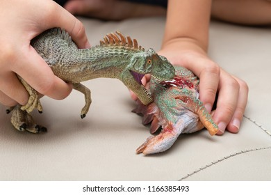 kid playing with toys of allosaurus and stegosaurus bloody body on sofa at home