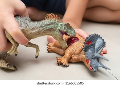 kid playing with toys of allosaurus and triceratops bloody body on sofa at home