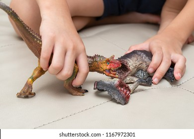 kid playing with toys of Carnotaurus and dinosaur bloody body on sofa at home