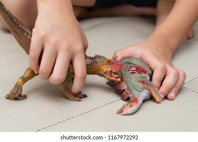 kid playing with toys of Carnotaurus and stegosaurus bloody body on sofa at home