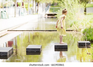 kid playing in urban environment. child jumping on stones across town pond. blond little girl in dress exploring city water space.