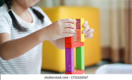 Kind, das mit Holzspielzeug spielt. Kleinkindermädchen baut Burg mit Würfeln. Kleines Mädchen und lustig mit pädagogischen Spielzeugblöcken. Kinder spielen in der Tagesbetreuung oder Vorschulzeit.