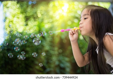 Kid pLAYLING BLowing Bubbles Together at the Field