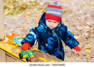 the kid plays cars in the sandbox on the street