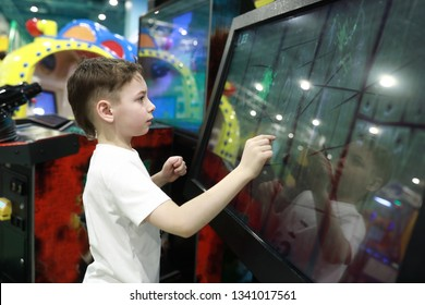 Kid plays game on large touch screen in amusement park