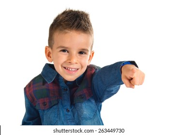 Kid pointing to the front over white background