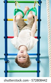 Kid preschooler boy on the gymnastic rings in the gym class
