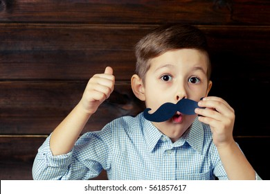 A kid with props for a photobooth gives a thumbs-up. Surprised child with the requisite mustache on wooden background. Little boy approves .
