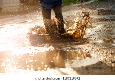 kid in puddle, splashing in puddle