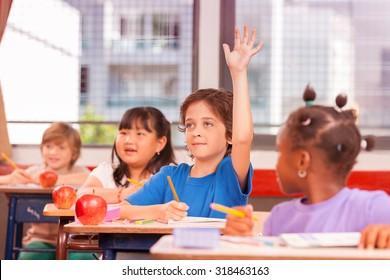 Kid raising hand in elementary school.