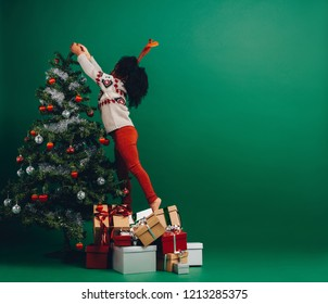 Kid reaching for the top of a christmas tree to decorate. Little girl decorating a christmas tree standing on gift boxes.