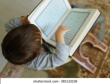 Kid reading Koran (the page is blurred)