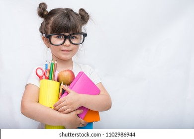 Kid ready for school. Cute clever child in eyeglasses holding school supplies: pens, notebooks, scissors and apple. Back to school concept. Space for text, isolated on white.