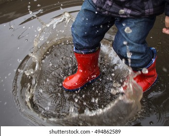 kid in red rubber boots make of water splashes in a puddle