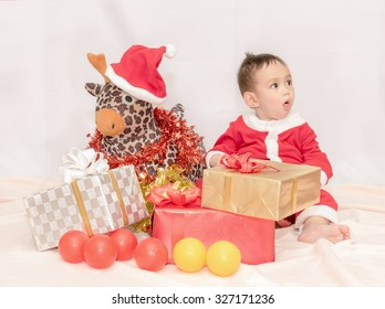Kid in the red Santa Claus suit sitting with reindeer doll among the gift boxes