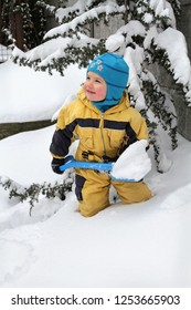 Kid removes snow with a toy shovel