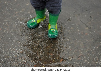 Kid with rubber boots in puddle in rainy autumn day