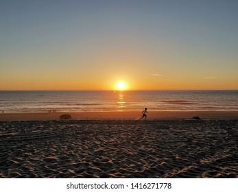 A kid runnuing on the beach at sunset at Mira Beach (Praia de Mira) Portugal