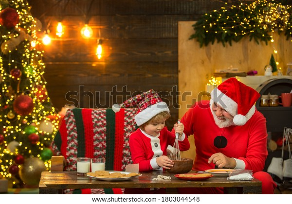 Kid Santa Claus enjoying in served gingerbread cake and milk. Santa Father and son having fun near Christmas tree and celebrate christmas at home. Funny kid make Christmas cookies