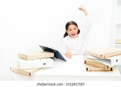 Kid school uniform happy face read book. Excited about knowledge. Homeschooling concept. Interesting book for children. Girl child read book sit table white interior. Schoolgirl studying textbook.