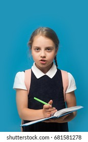 Kid in school uniform isolated on blue background.