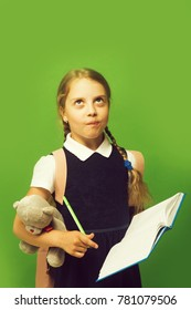 Kid in school uniform isolated on green background. Girl with braids and thoughtful face expression. Study and back to school concept. Pupil holds blue book, marker and teddy bear