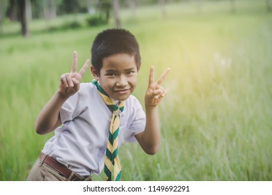 Kid scout stand and lift finger two fingers and make faces.on green grass ,on forest background.